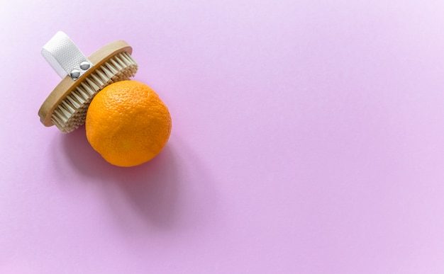 Brosse corporelle et grosse orange pour massage anti-cellulite sur fond rose