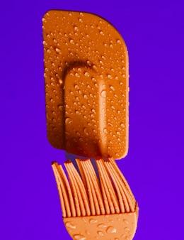 Brosse de cuisine en silicone et spatule pour cuisiner en gouttes d'eau sur fond violet