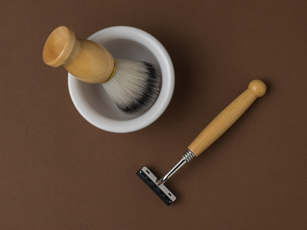 Une brosse dans un bol blanc et un rasoir avec un manche en bois sur fond marron. mise à plat.