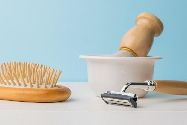 Une brosse dans un bol blanc, un rasoir et un peigne sur une table blanche sur fond bleu.