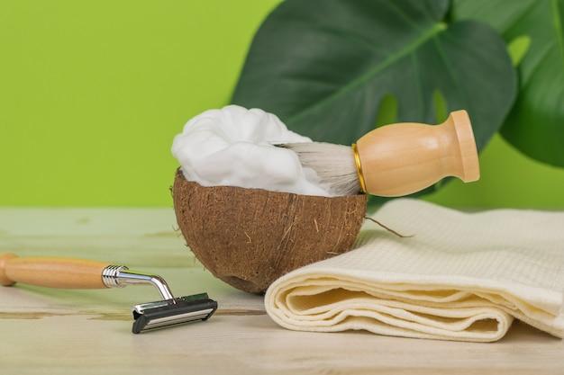 Une brosse dans un bol de noix de coco avec de la mousse à raser et un rasoir sur fond vert.