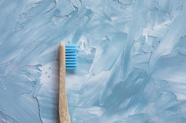 Une brosse à dents en bambou bleu. concept sans plastique, zéro déchet. vue de dessus, fond blanc et bleu, espace copie