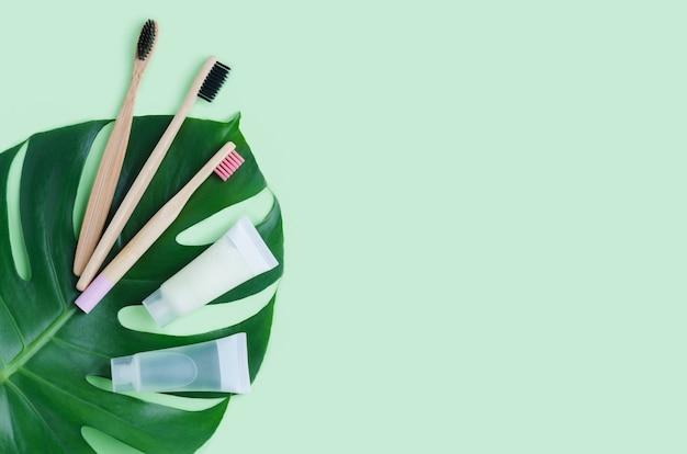 Brosse à dents en bambou, dentifrice à base de plantes pour soins bucco-dentaires sur feuille de monstera. zéro déchet, sans plastique dans une maison écologique.