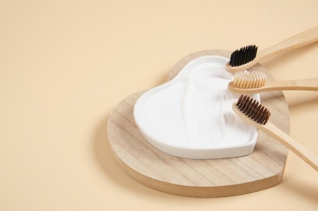 Brosse à dents en bambou écologique. brosses à dents en bambou et bicarbonate de soude sur fond beige concept de style de vie zéro déchet. se brosser les dents avec du soda