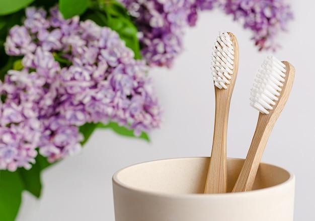 Brosse à dents en bambou écologique dans une tasse avec des fleurs lilas sur blanc