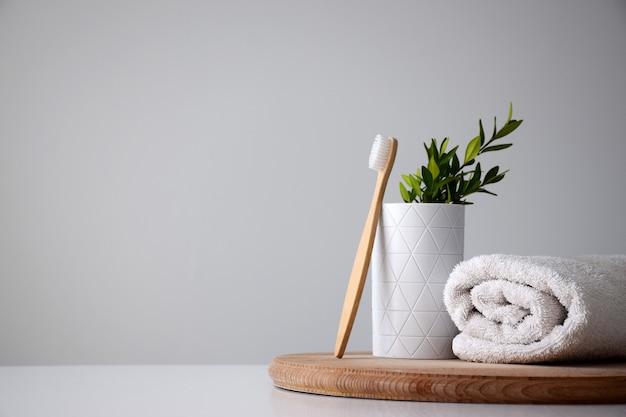 Brosse à dents en bambou écologique près du support blanc et serviette roulée blanche sur planche ronde en bois