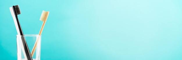 Brosse à dents en bambou naturel écologique et deux brosses à dents en plastique dans un verre sur une surface bleue