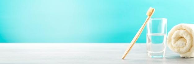 Brosse à dents en bambou, verre d'eau, serviette en coton blanc avec espace pour le texte