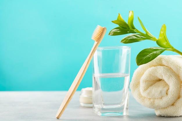 Une brosse à dents en bambou, un verre d'eau, une serviette en coton blanc et de la poudre de brosse à dents dans un bocal