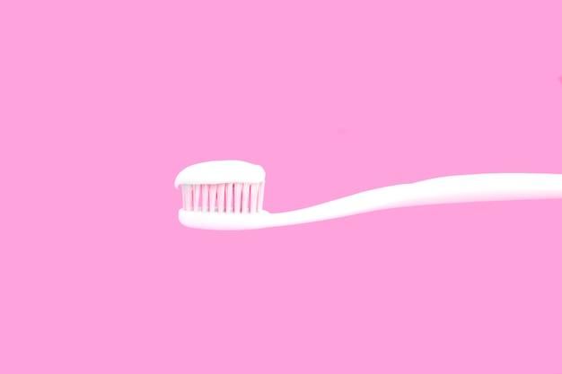 Brosse à dents blanche avec un dentifrice sur fond rose