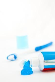 Brosse à dents bleue à côté d'un tube de dentifrice