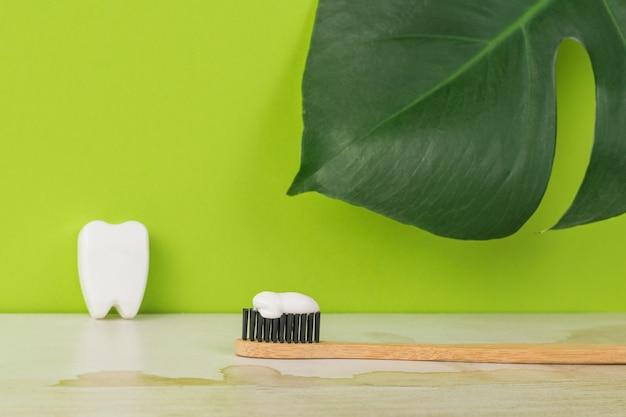 Brosse à dents en bois avec pâte sur fond de feuilles vertes.