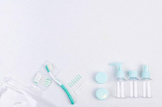 Brosse à dents et contenants en plastique pour les voyages sur fond blanc et baguettes. pose à plat