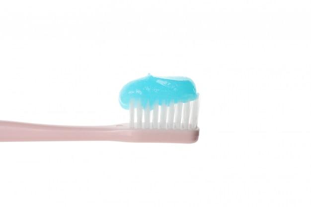 Brosse à dents avec du dentifrice isolé sur une surface blanche