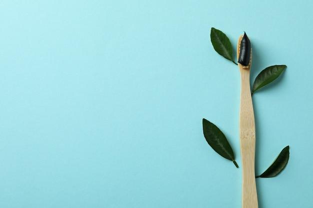 Brosse à dents écologique avec du dentifrice et des feuilles sur bleu