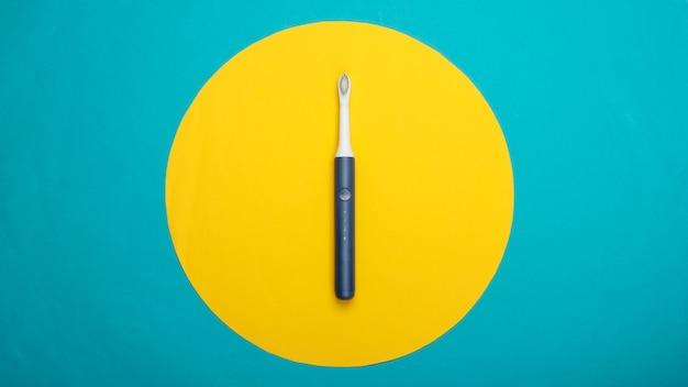 Brosse à dents électrique moderne sur surface bleue avec cercle jaune