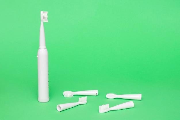 Brosse à dents électrique sans fil blanche avec têtes remplaçables sur fond vert clair copy space