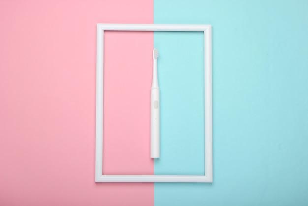 Brosse à dents électrique sur surface pastel bleu rose avec cadre blanc