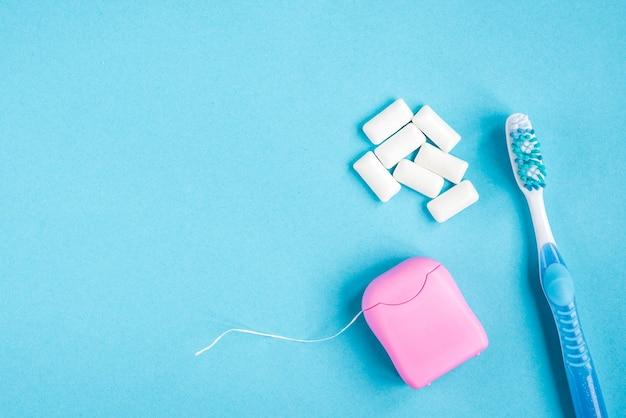 Brosse à dents, fil dentaire et gomme sur fond bleu. nettoyage et protection des dents