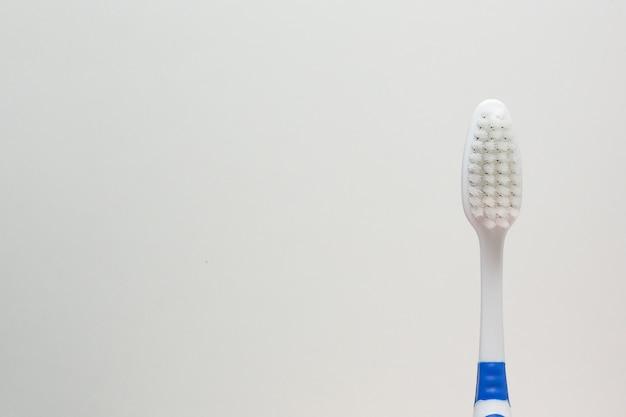 Une brosse à dents sur fond blanc bouchent l'image.