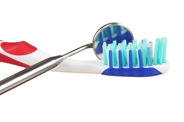 Brosse à dents et instruments dentaires isolés sur une surface blanche