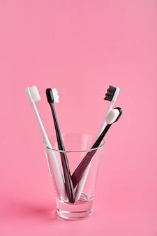 Brosse à dents à la mode avec des poils doux. brosses à dents populaires. tendances d'hygiène. kit de brosses à dents en verre sur fond rose.