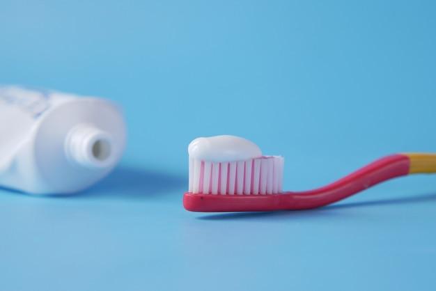 Brosse à dents avec de la pâte sur fond bleu