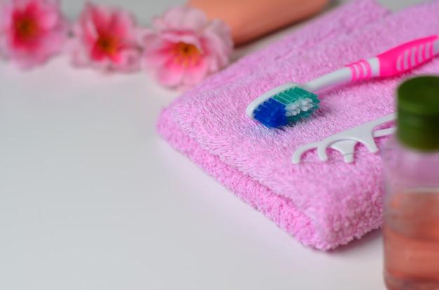 Brosse à dents rose et un cure-dent en plastique sur une serviette rose.