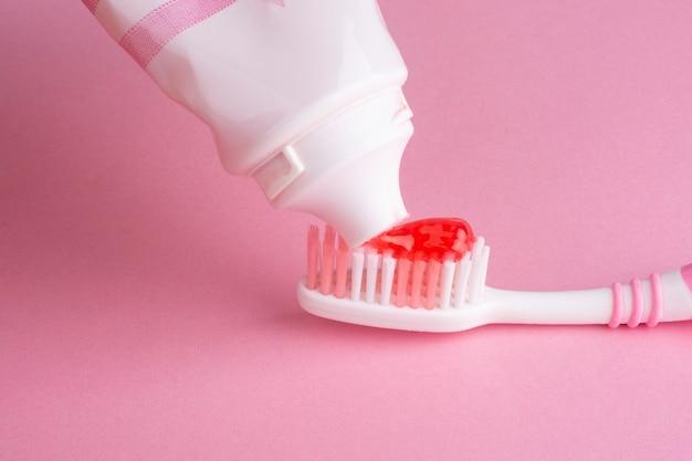 Brosse à dents rose et tube rose de dentifrice.