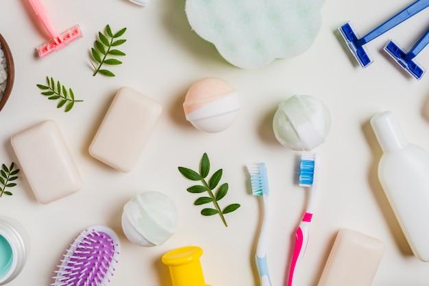 Brosse à dents; savon; bombe de bain; rose; produits de rasoir et cosmétiques sur fond blanc