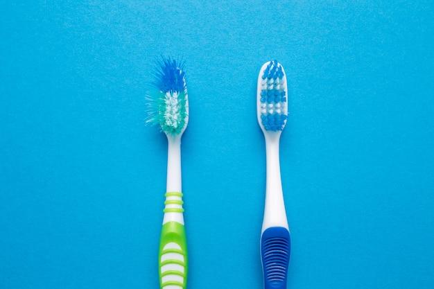 Brosse à dents usagée ancienne et neuve sur un mur bleu.