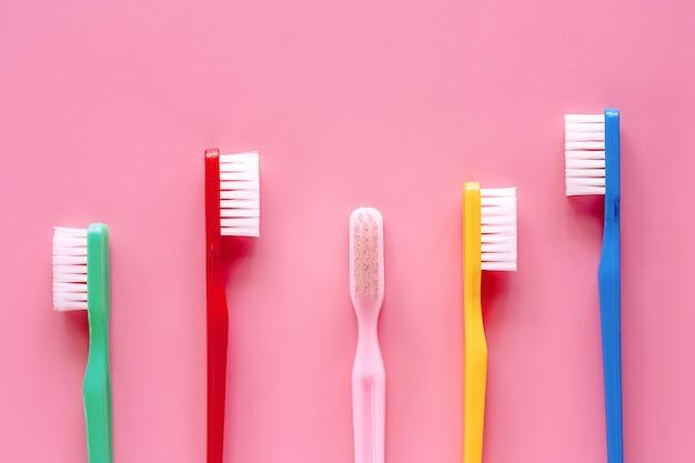 Brosse à dents utilisée pour nettoyer les dents sur fond rose