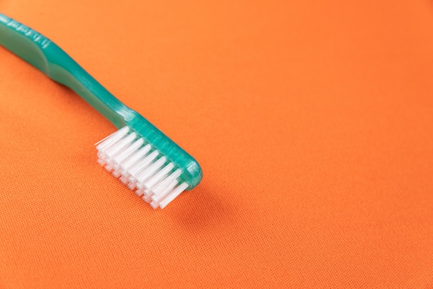 Brosse à dents verte sur la table orange