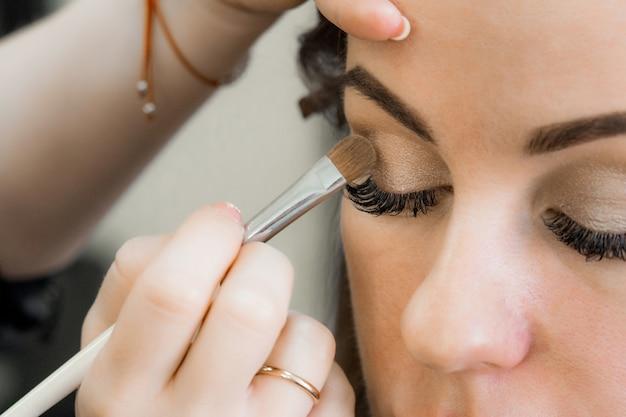 Brosse avec fard à paupières dans les mains d'une maquilleuse aux yeux d'une fille dans un salon de beauté