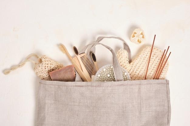 Brosse de massage, bâtons d'arôme, luffa, brosses à dents en bambou, bâtonnets d'arôme et savon de cacao maison dans un sac en tissu sur un fond texturé beige clair