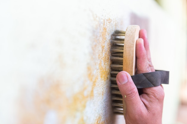 Brosse métallique en laiton nettoyant un mur