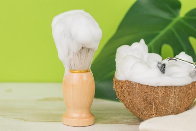 Une brosse et une mousse à raser épaisse dans un bol en noix de coco.