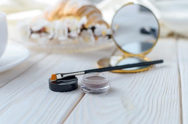 Brosse et ombres (rouge à lèvres) pour les sourcils sur la table basse