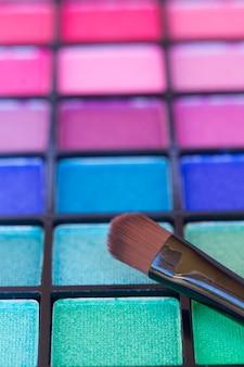 Une brosse sur la palette d'ombres à paupières colorées