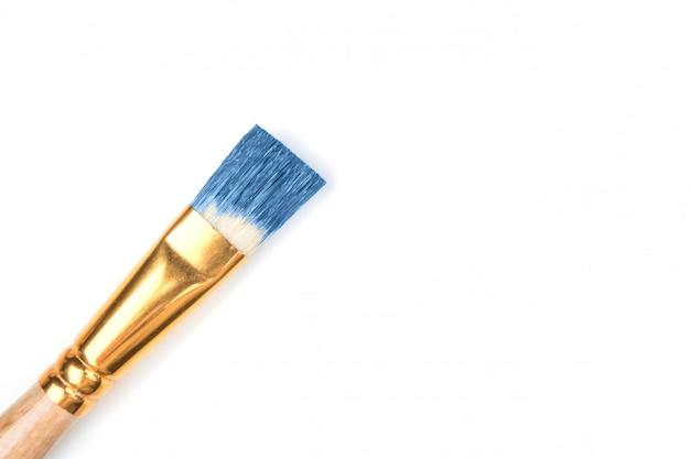 Brosse à poils naturels en peinture bleue sur fond blanc isolé.