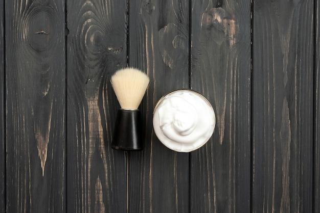 Brosse à raser et crème sur fond de bois foncé
