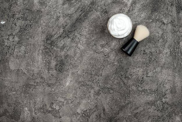Brosse à raser et crème sur fond gris foncé, paster