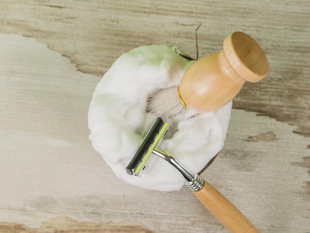 Une Brosse Et Un Rasoir Avec Des Manches En Bois Dans Un Bol En Noix De Coco Avec De La Mousse à Raser. Mise à Plat. Photo Premium
