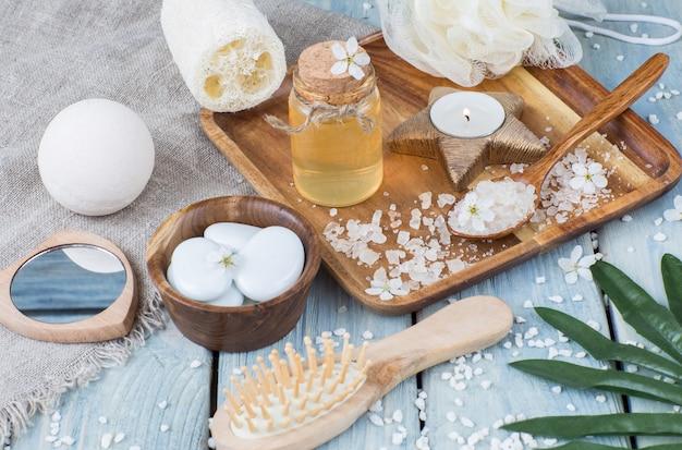 Brosse, sel dans une cuillère, huile, gant de toilette, pierres, miroir - articles de spa