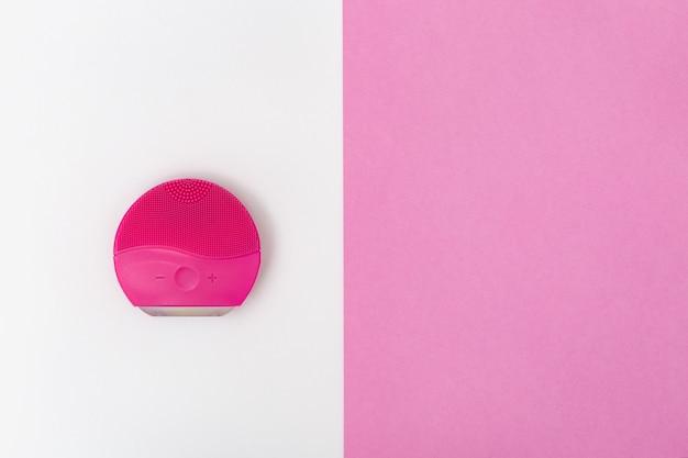 Brosse en silicone pour lavage du visage sur rose et blanc