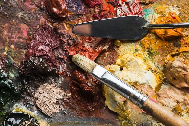 Brosse et spatule sur une palette rugueuse