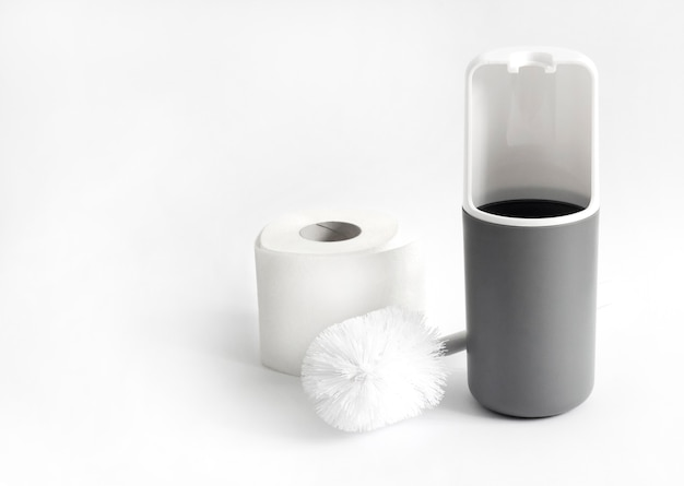 Brosse de toilette en plastique blanc et gris et rouleau de papier toilette sur fond blanc. copier l'espace