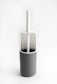 Brosse de toilette en plastique blanc et gris sur surface blanche