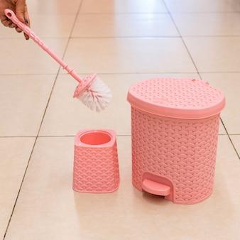Brosse de toilette rose et support, poubelle isolé