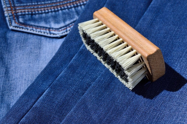 Une brosse à vêtements repose sur un jean plié.